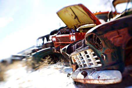 heavily: old cars in the snow at a rural junkyard. limited depth of field with focus on front grill. legal note - license plate heavily modified.