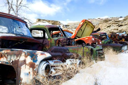old classic and vintage cars in the snow at a junkyard in rural Wyoming photo