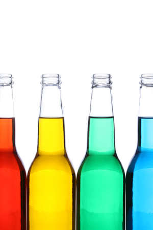 glass bottles with red, yellow, green, and blue liquids, shot closeup isolated on white photo