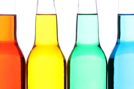 glass bottles with red, yellow, green, and blue liquids. closeup isolated on white photo