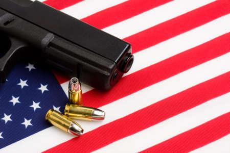 gun control: gun over american flag, modern 9mm handgun with bullets