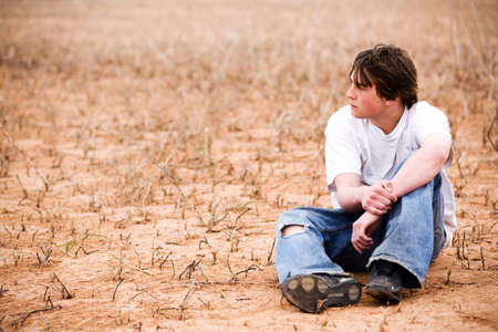 teenager sitting outdoors in wilderness area, dry lakebed among the weeds