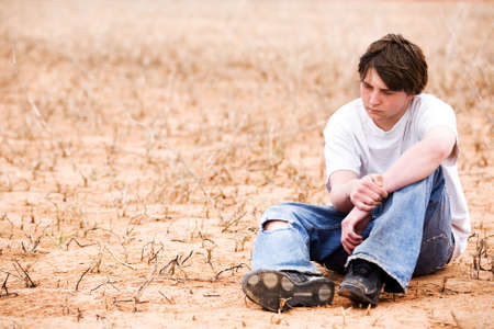 teenager sitting depressed in dry lakebed amongst the weeds, contemplating. Stock Photo - 3008321