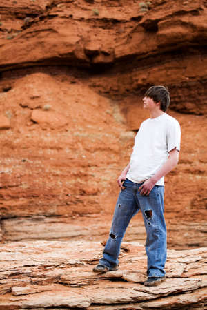 teenager standing on a rock in the mountains of wyoming. Muddy shoes, holes in jeans, hands in pocket.  Stock Photo - 3008323