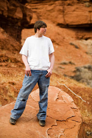 teen male in nature wilderness area, standing on a rock with holes in jeans, hands in pockets. Stock Photo - 3008318