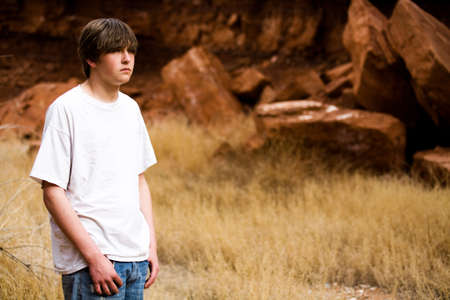 teen boy in Wyoming wilderness area, large red-brown boulders in background, copyspace photo
