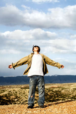 atop: freedom - teenager male with arms wide open, shirt and hair blowing in the wind, standing atop a 1,000 foot cliff Stock Photo