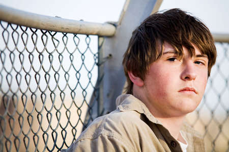 teenager male with natural look sitting against fence looking into camera Stock Photo - 3008920