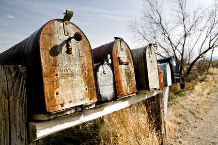 postmaster: Old vintage mailboxes in rural Midwest United States, late sun
