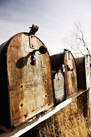 postmaster: Old American mailboxes in late sun, rusting away in rural Midwest.