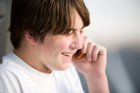 teenager male on cellphone laughing. A natural portrait. Stock Photo - 3013741