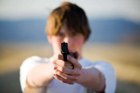 teenager pointing modern 9mm handgun at camera, shallow depth of field with focus on front of gun