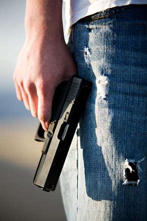 Teen male holding modern 9mm handgun, limited depth of field closeup