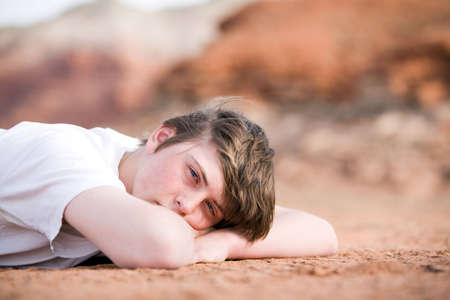 teenager male laying on the ground outdoors, natural light with mountains in background Stock Photo - 3020506