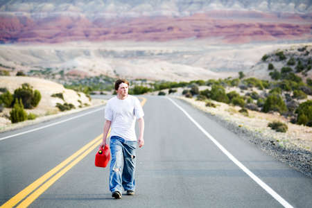 gas can: teenager out of gas, walking down rural mountain road with gas can