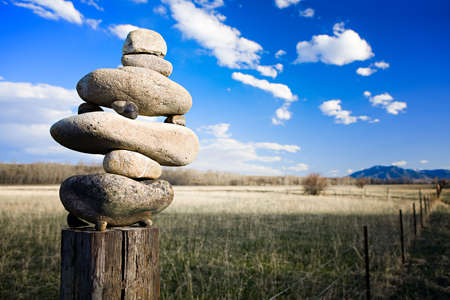 zen western style - stones balancing on a fencepost in rural Montana Stock Photo