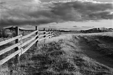 fencepost: fence running through the landscape of Wyoming, coverted to black and white