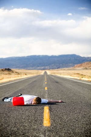 out of gas - teen male laying dead in the middle of a remote rural highway still clinging to red gas can photo