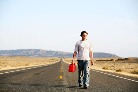 gas can: out of gas - teenager male walking down rural highway with empty red gas can