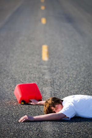 irresponsible: out of gas - teen with empty gas can lies dead in the middle of the road Stock Photo