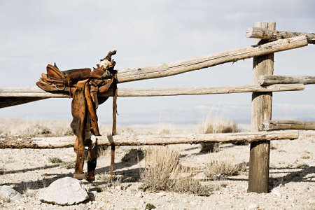western culture: ranch scene - saddle on rural fence, vintage worn saddle in the dry and barren countryside