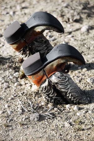 cowboy boots: vintage cowboy boots buried upside down in the dirt Stock Photo
