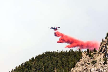 retardant: antincendio aeromobili di dumping rosso ignifugo chimico pi� di foresta Montana durante la lotta antincendio sforzo per contribuire a contenere la diffusione fuoco
