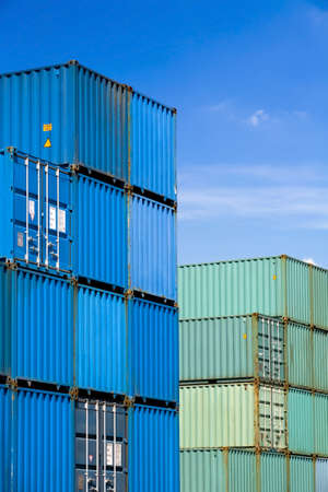 shipping cargo containers stacked under a blue sky at freight terminal Stock Photo