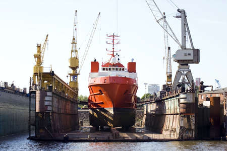 pier: ship for repairs in large floating dry dock