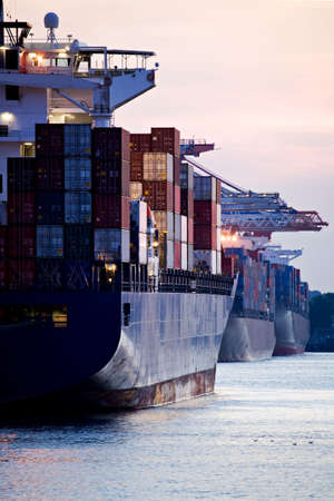 docked: los buques de carga de contenedores atracado en el puerto - tres enormes aviones de carga en puerto terminal durante la puesta de sol
