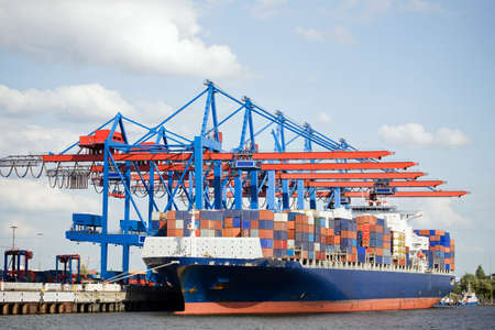 container ship in port terminal - huge freighter fully loaded