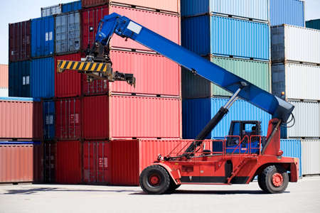 handler: containers stacked in port with container handler  forklift on the move Stock Photo