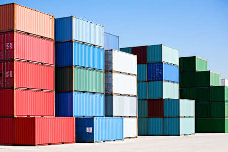 containers: cargo shipping containers stacked at harbor freight terminal under clear blue sky Stock Photo