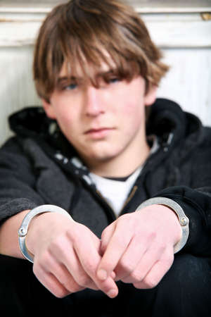 youth crime - teenage in handcuffs against wall. Focus on handcuffs. Stock Photo - 3897743