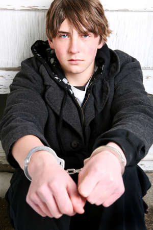 juvenile delinquent: teen crime - teenager with remorseful look in handcuffs against wall Stock Photo