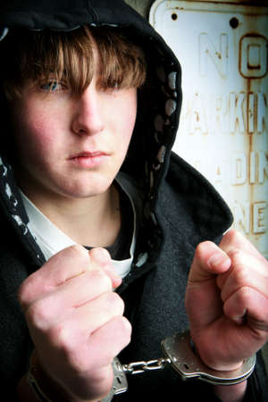 delinquent: teenager in handcuffs closeup against a wall Stock Photo