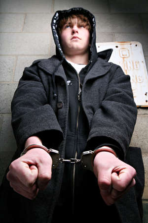 juvenile delinquent: teenager in handcuffs against wall. Focus on handcuffs. Stock Photo