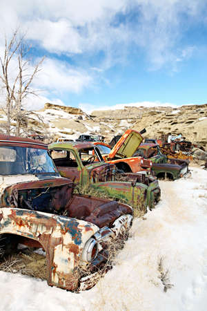 abandoned vintage classic cars in junkyard during winter photo