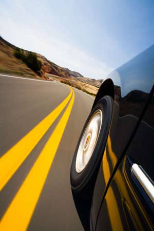 car driving: car driving on mountain road - low angle with natural motion blur, focus on wheel