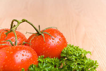 kitchen counter top: tomatoes and parsley with water droplets on wooden kitchen counter top Stock Photo
