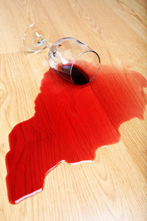 mishap: wine spilled on hardwood floor - red wine glass Stock Photo