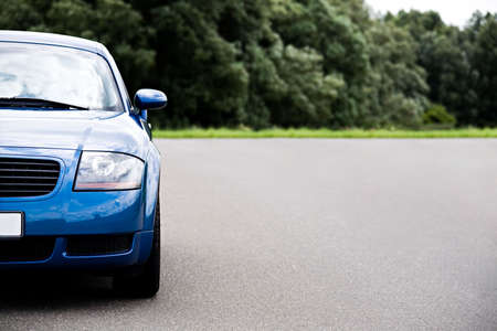 sports car - modern blue coupe on road, focus on headlight with ample copyspace Stock Photo