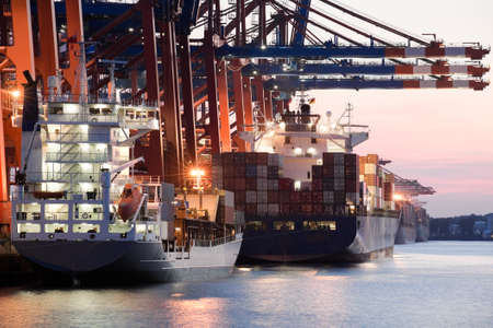 hamburg: ships in harbor - giant freighters in port being loaded with containers, setting sun