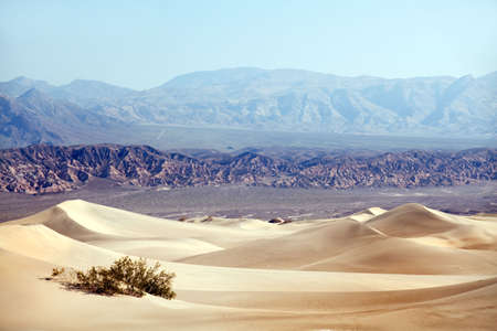 desert dunes with mountains in background - death valley national park california usa photo