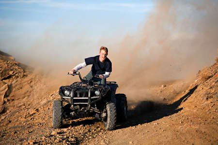teenager male riding a quad  four wheeler in rural Wyoming