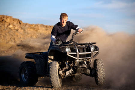 wheeler: male teenager riding a quad 4x4 - kicking up dust with his four wheeler Stock Photo