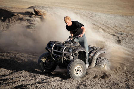 teenager male riding a quad  four wheeler 4x4 kicking up the dirt in rural hills Stock Photo
