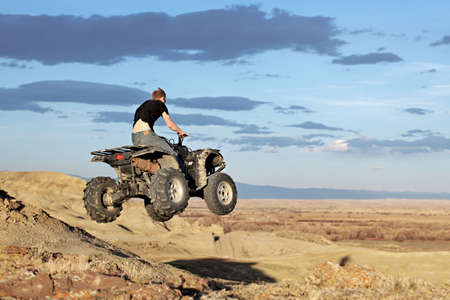 quad: teen jumping on a quad - four wheeler 4x4 gets some air Stock Photo