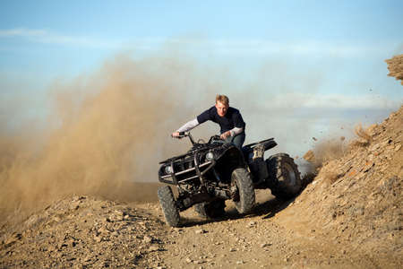 teen male riding a quad ATV - four wheeler in the hills of wyoming