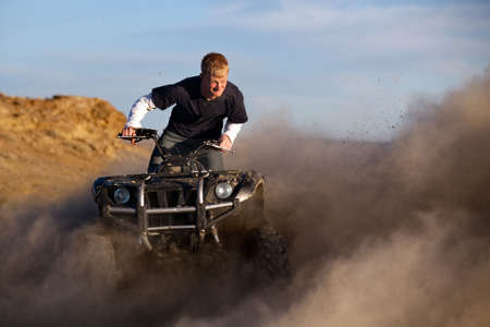 teen with funny expression on quad  ATV - four wheeler kicking up dust